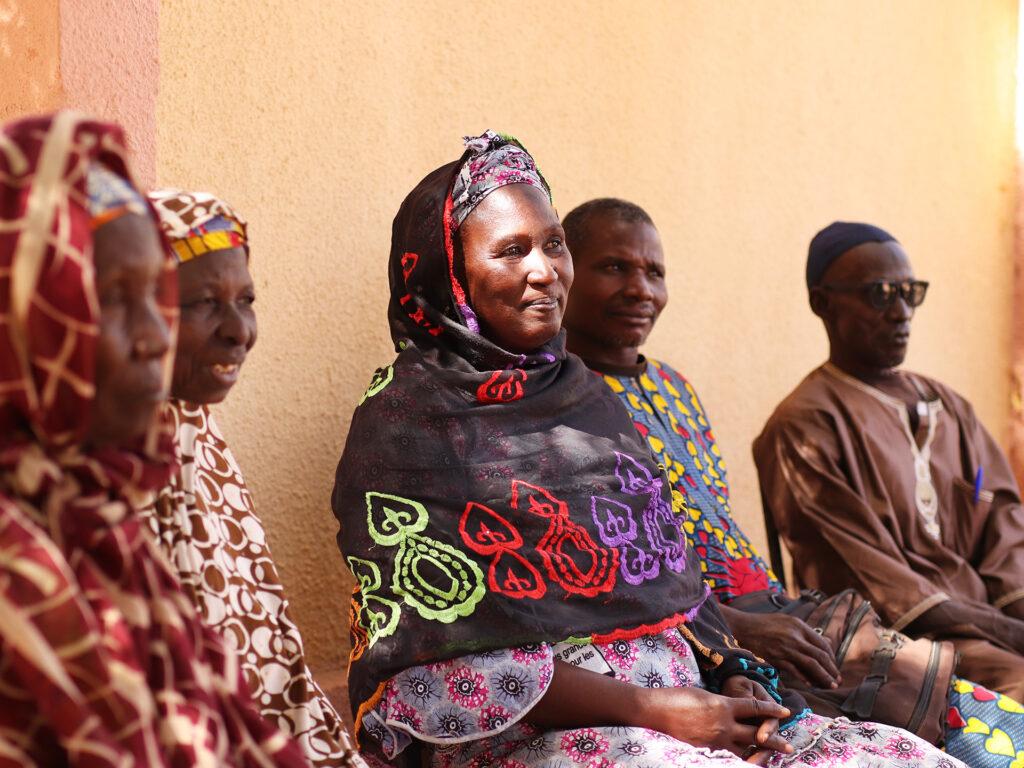 En kvinna sitter leende mot en husvägg tillsammans med en grupp andra människor.