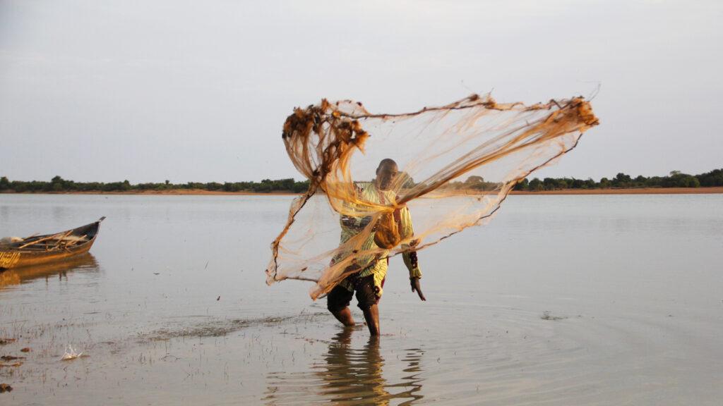 En fiskare står i vattnet och kastar ett nät