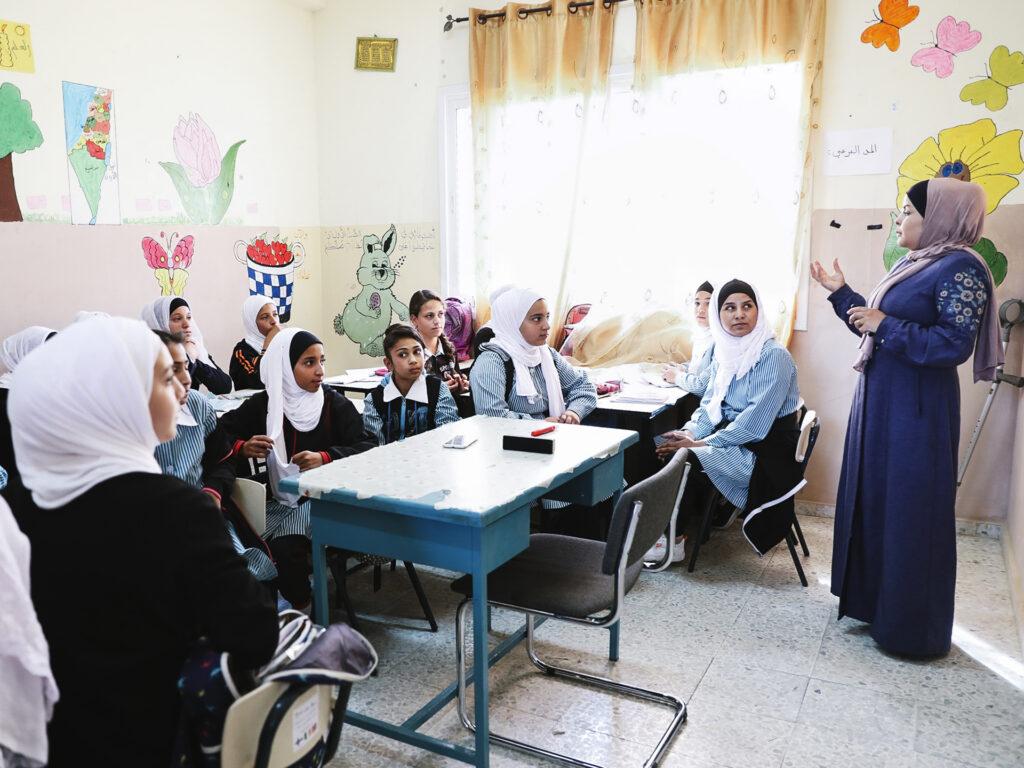 Ett klassrum i Palestina med unga flickor och en lärare. Väggarna är målade med olika motiv.