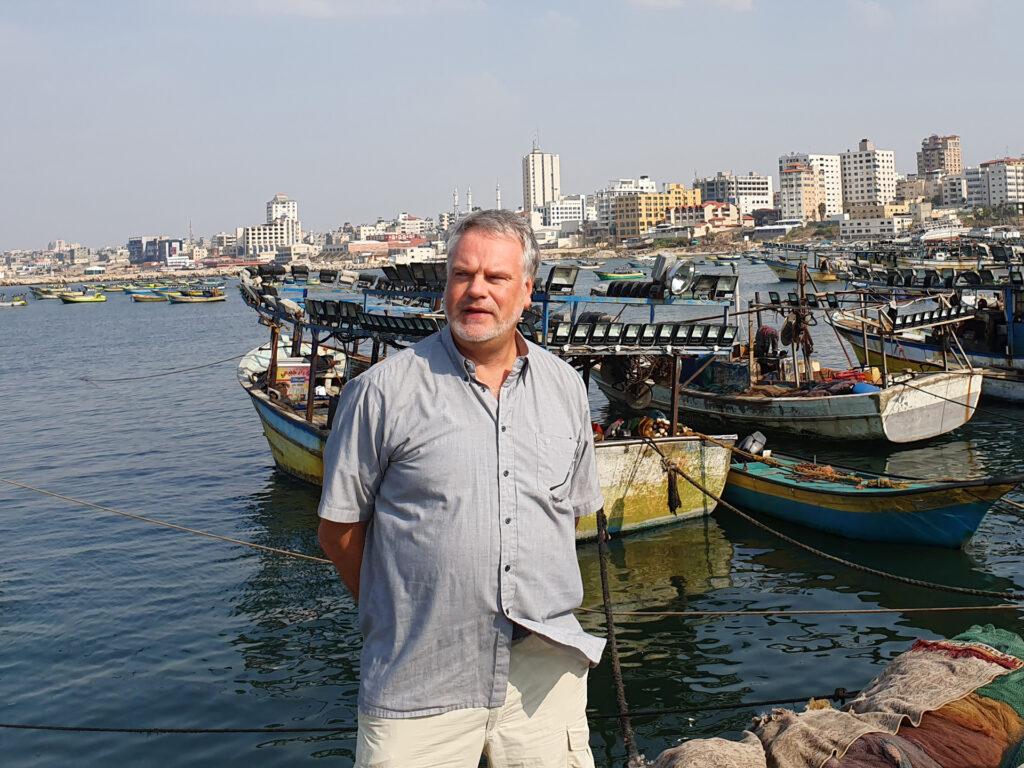 En man på en kajkant med små fiskebåtar och stora hus i bakgrunden