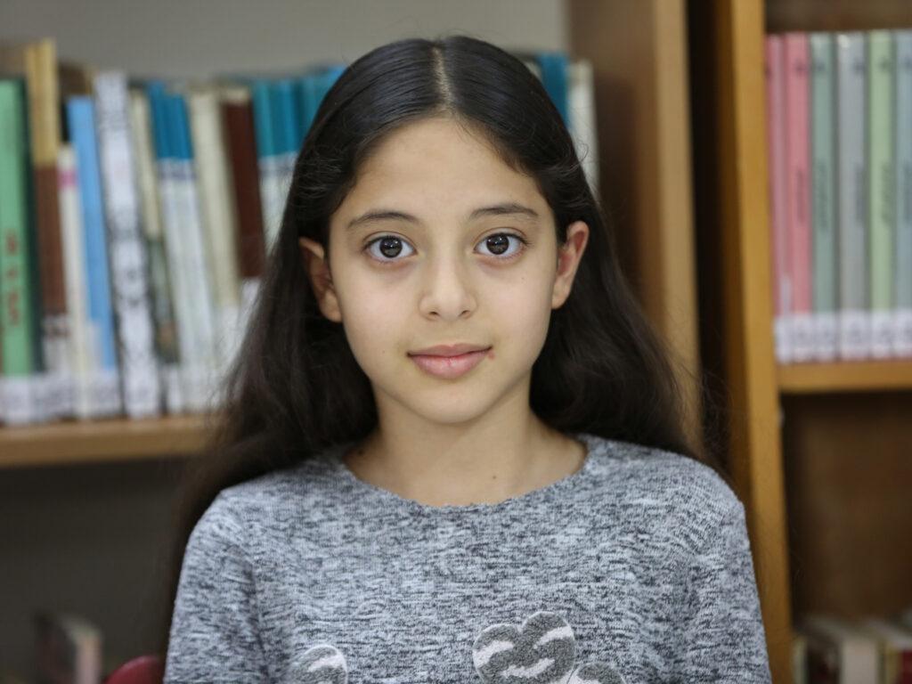 En flicka framför en bokhylla tittar in i kameran