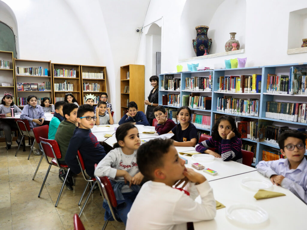 Barn sitter vid ett bord i ett bibliotek