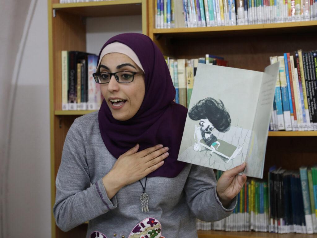 En kvinna i ett bibliotek visar en bilderbok och läser