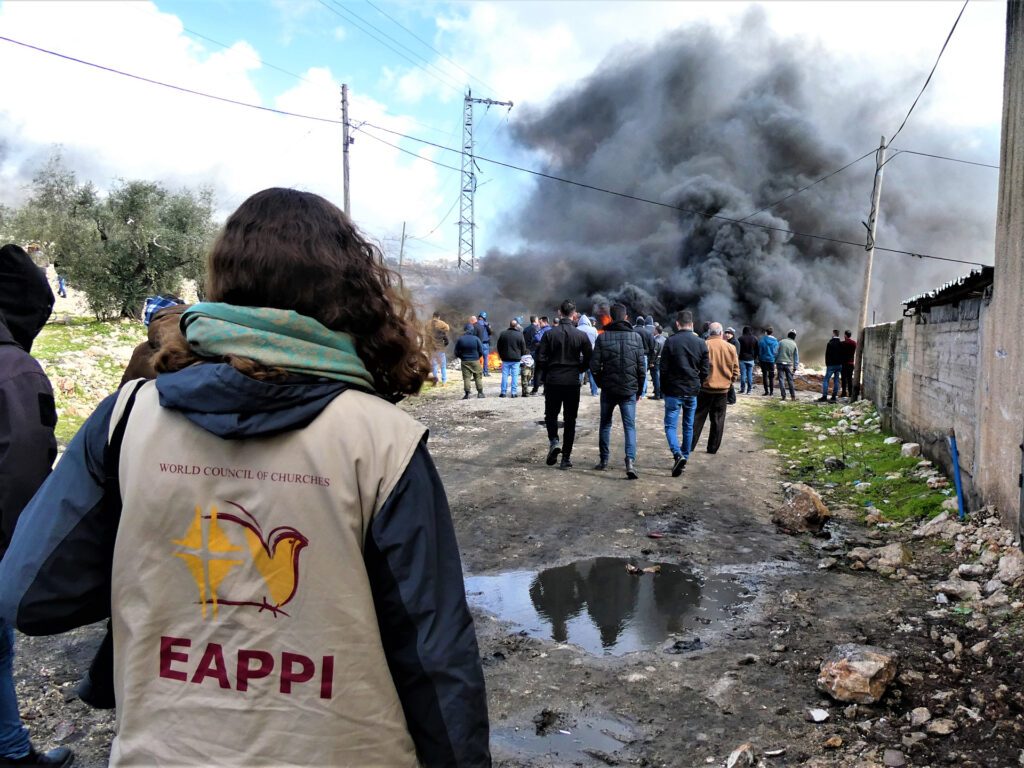 Ryggen på en kvinna med väst från följeslagarprogrammet och människor och en explosion längre bort