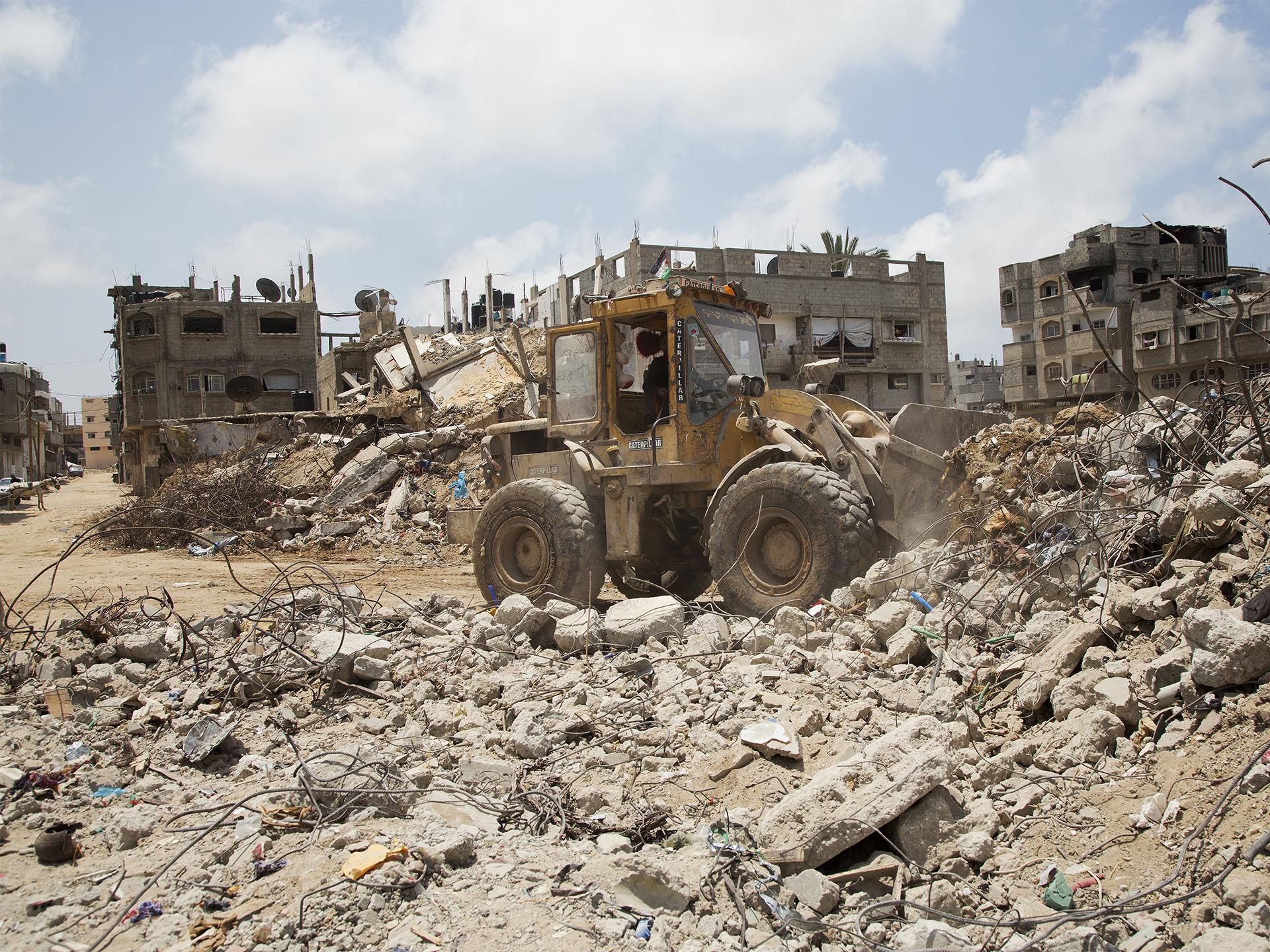 Traktor röjer framför bombade bostadshus i Gaza
