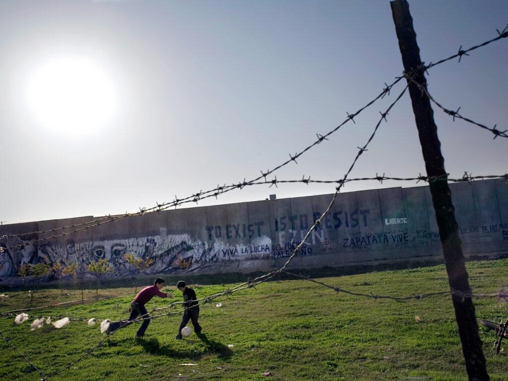 Två barn spelar fotboll framför muren i Palestina