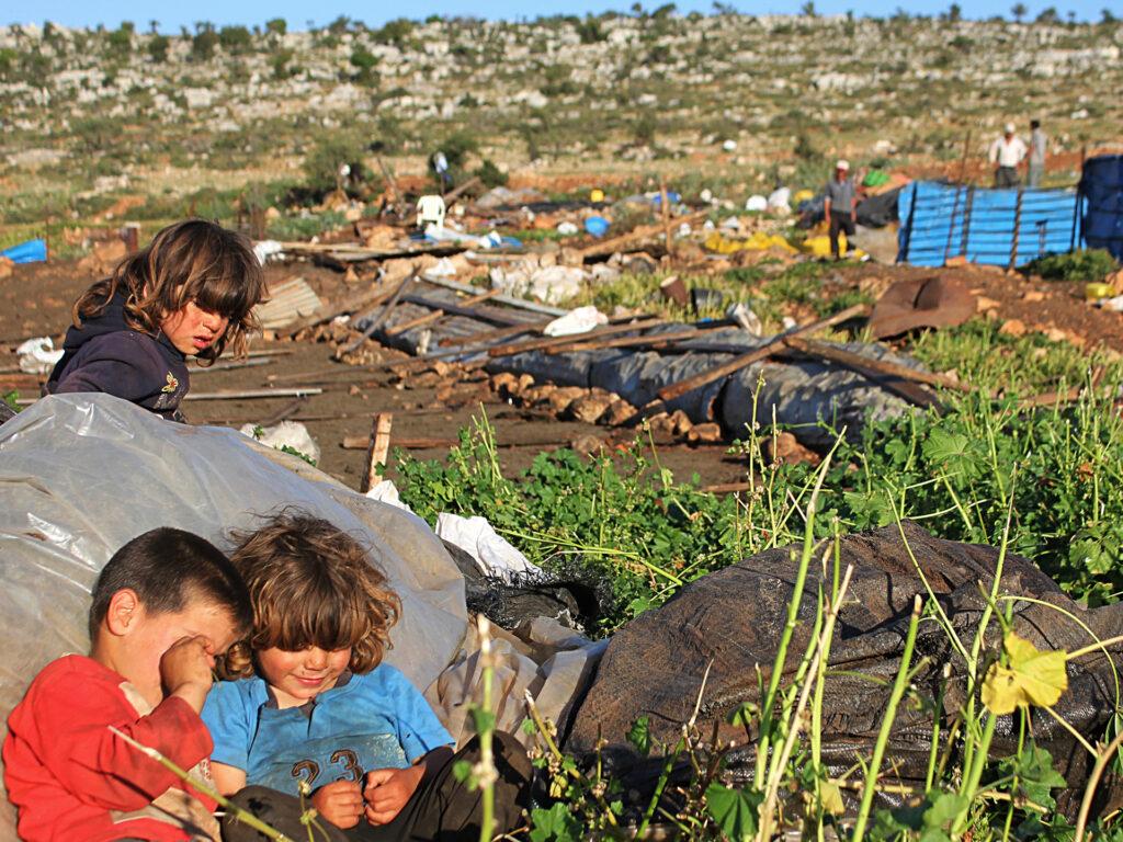 Tre barn vid förstörda byggnader