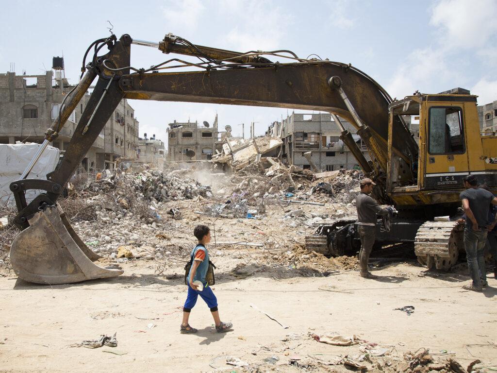 Pojke framför ruiner och grävskopa i Gaza