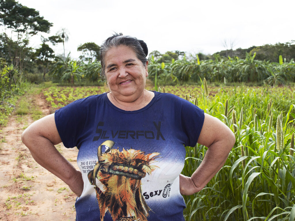 Kvinna står med armarna i sidorna i ett grönt fält.