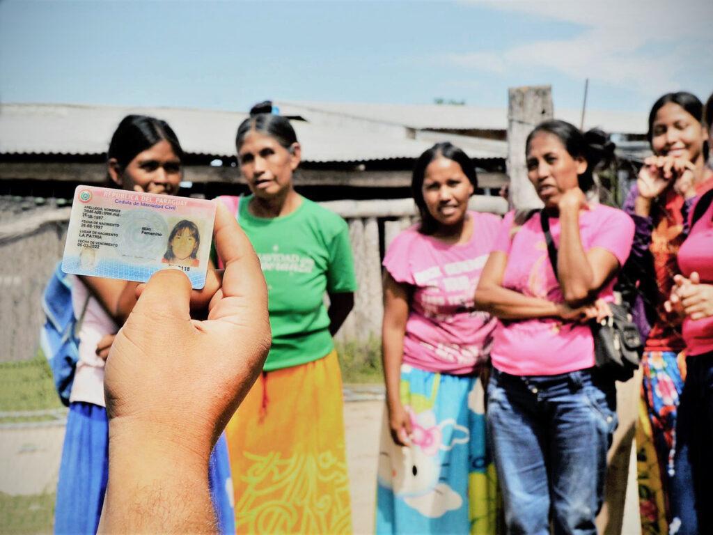 En grupp kvinnor står framför en hand som håller upp ett id-kort.