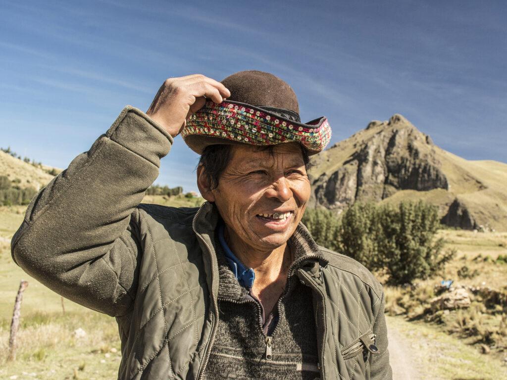 Porträtt av en äldre man med en hatt. I bakgrunden syns berg och slätter.
