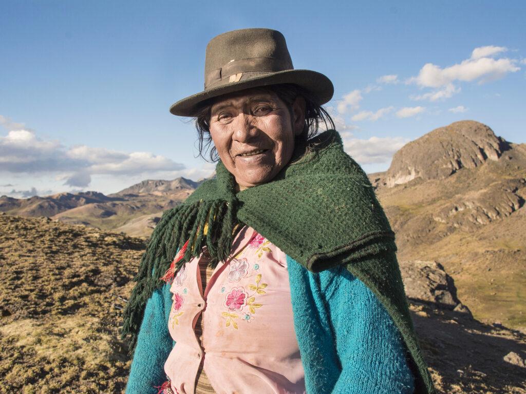 En äldre kvinna med hatt och sjal om axlarna står i ett landskap med berg och torra slätter.