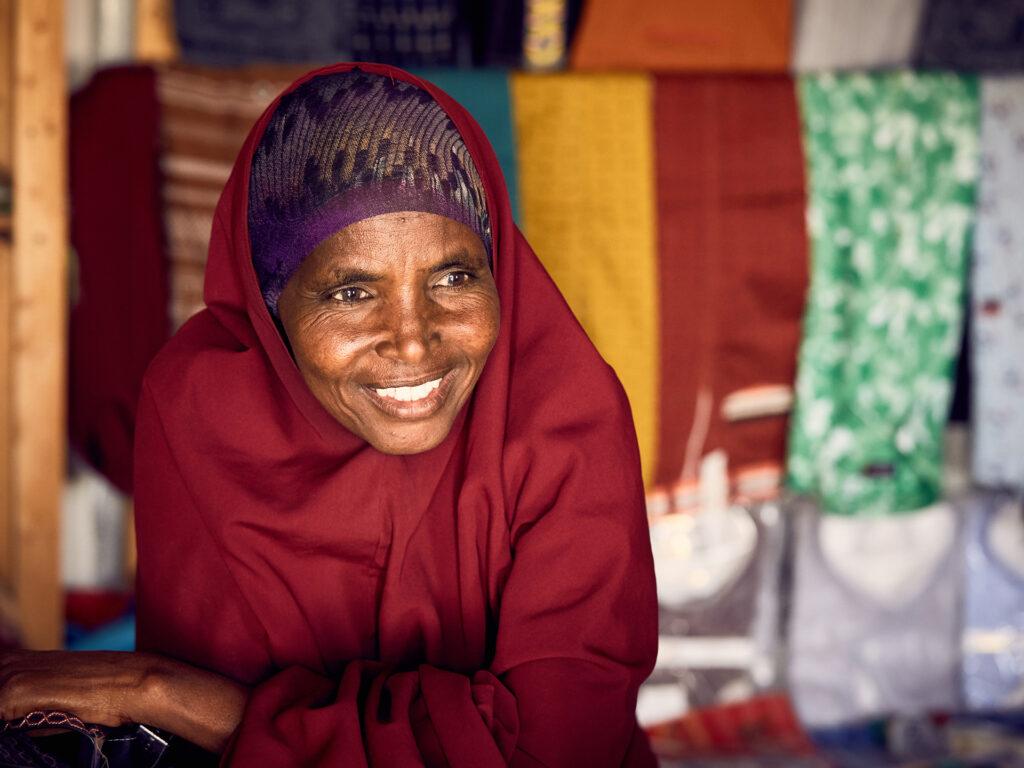 En leende kvinna i vinröd hijab.