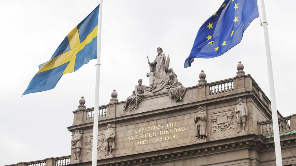 Svenska och europeiska flaggan framför riksdagshuset