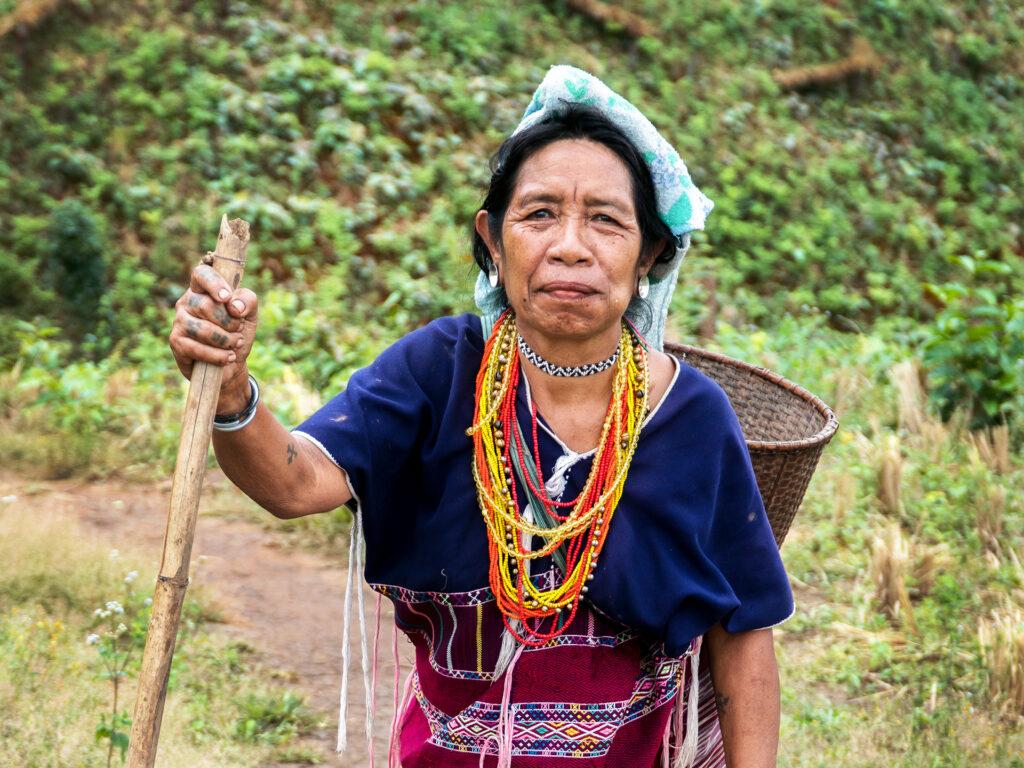 En thailändsk äldre kvinna med färgglada smycken står i ett grönt fält med en stav i handen. På ryggen har hon en korg.