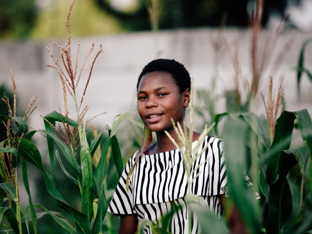 En flicka i ett majsfält tittar in i kameran