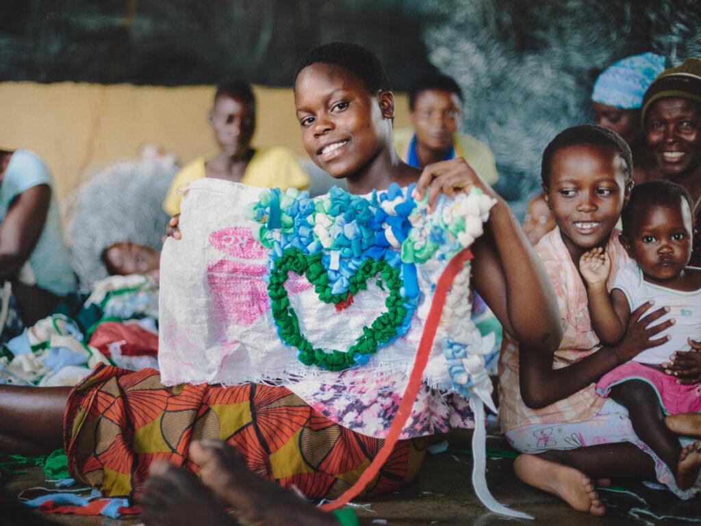 Barn sitter på golvet, en flicka visar upp ett tyg med ett sytt hjärta på