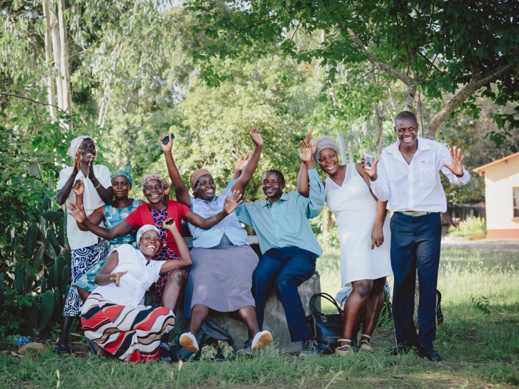 Ett gäng med glada kvinnor och män under ett träd