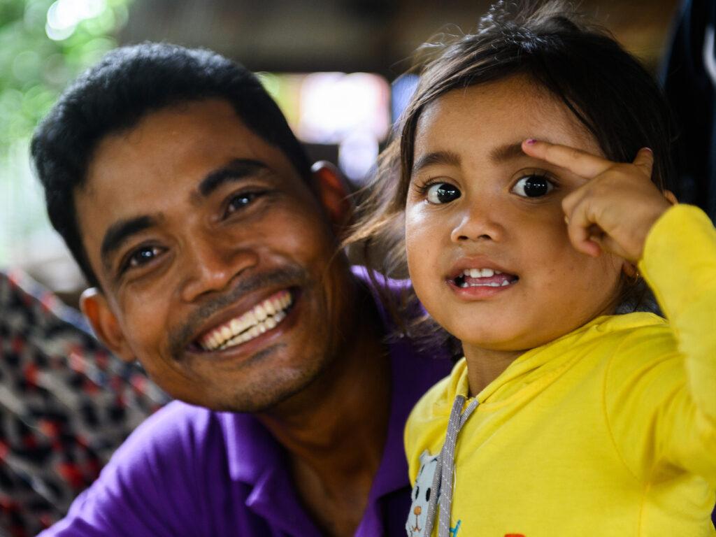 En pappa och dotter tittar in i kameran och ler.
