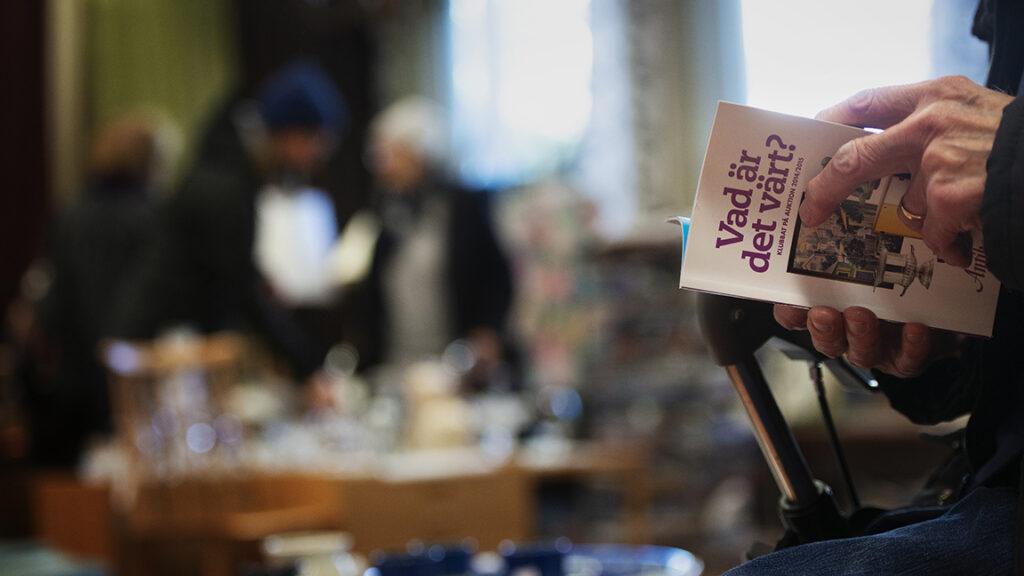 Bild på äldre persons hand som håller i en broschyr på en marknad