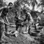 Fyra män vaskar grus i jakt på mineraler