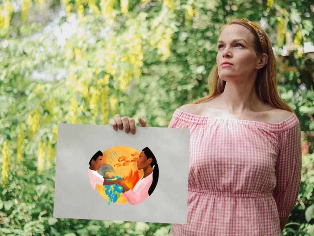 En kvinna håller en bild som visar människor vid naturkatastrof