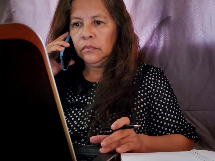 En kvinna sitter med en telefon mot örat framför en dataskärm.