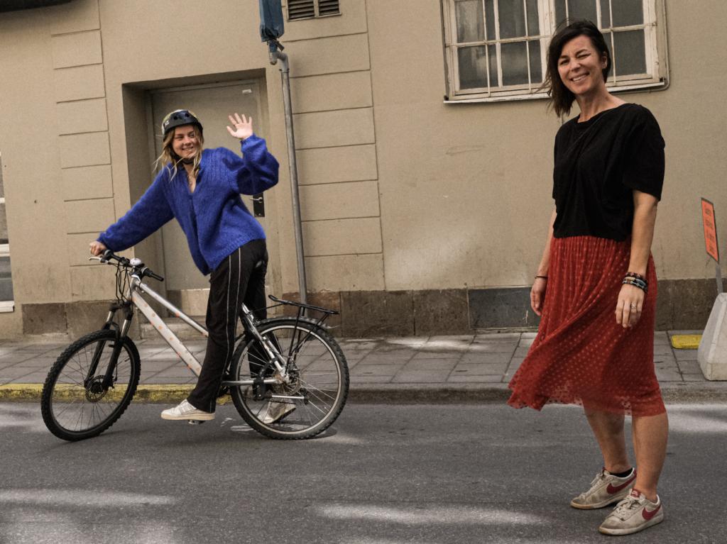 En ung tjej på cykel vinkar till en kvinna