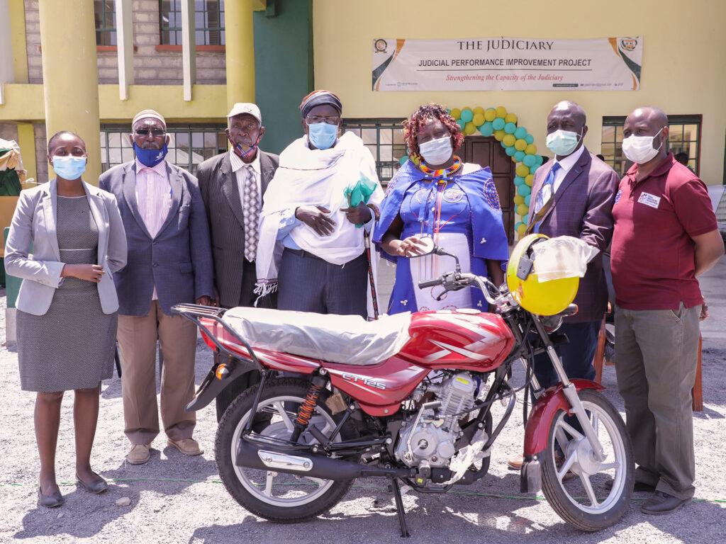 En grupp människor står framför en byggnad med en motorcykel framför sig.