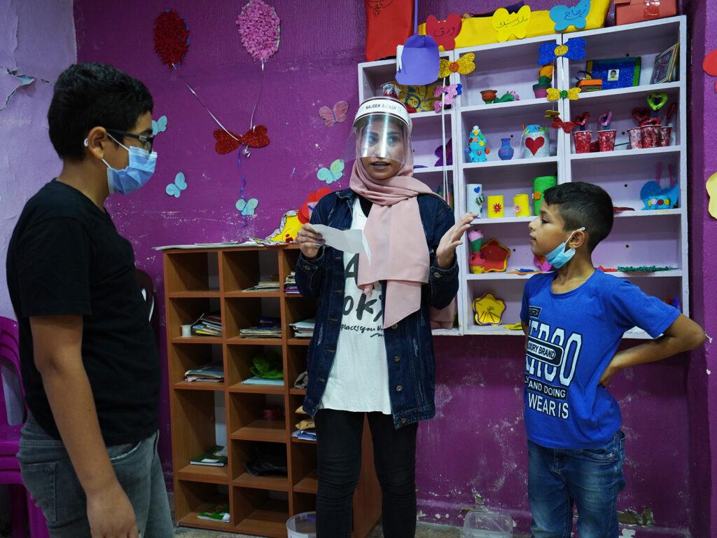 En lärare och två barn stor i ett rum med rosamålade väggar och bokhyllor med böcker.