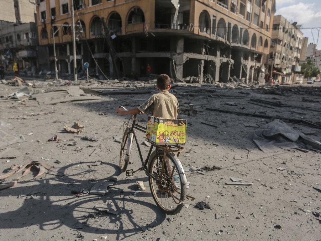 Ett barn står med en cykel och ryggen mot kameran, och ser mot ett sönderbombat hus.