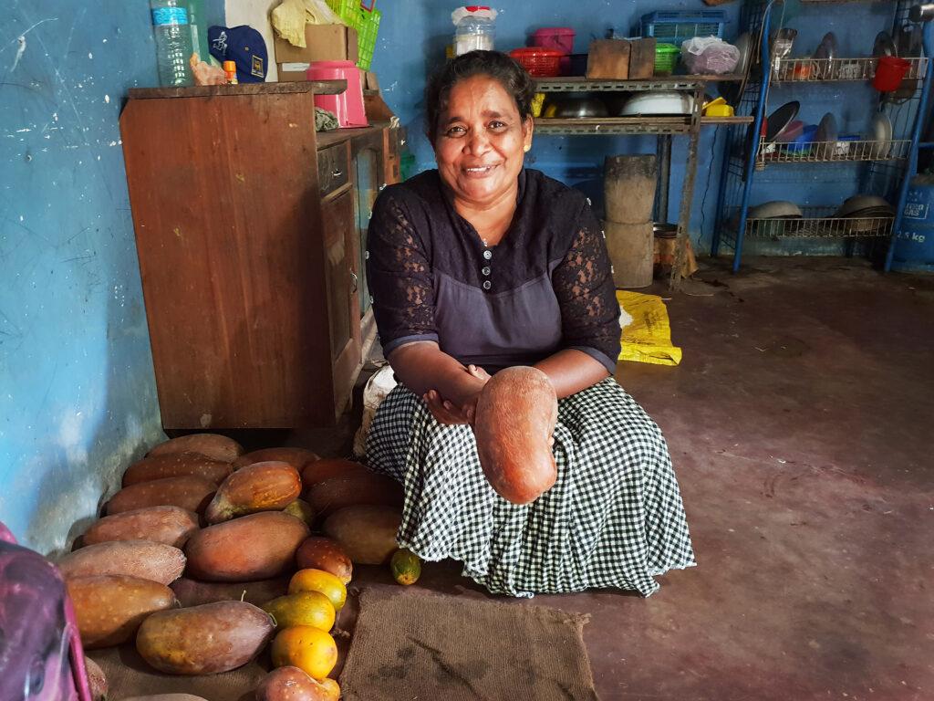 En kvinna sitter i ett rum med flera grönsaker framför sig. Hon ser in i kameran och ler.