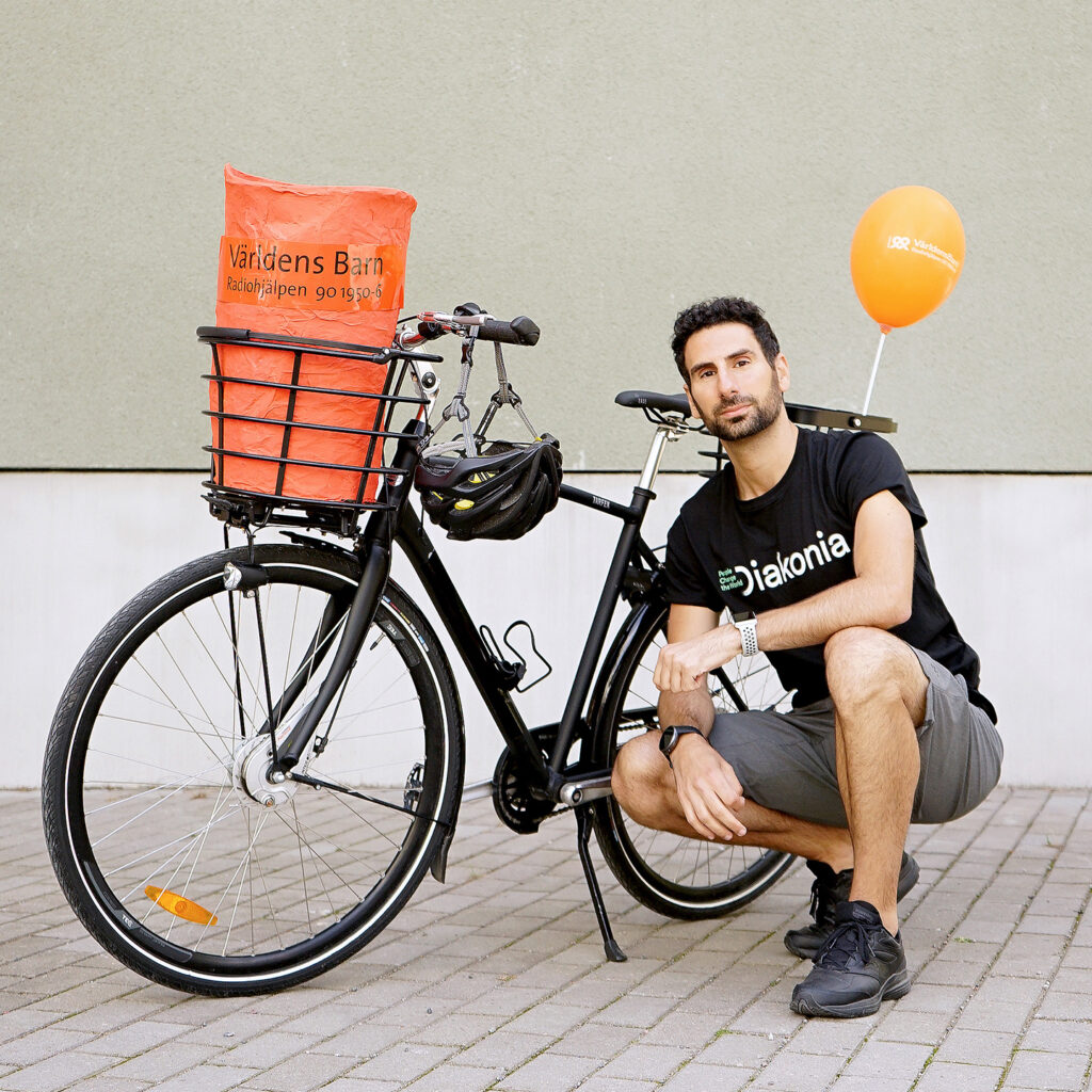 Man sitter på huk vid cykel