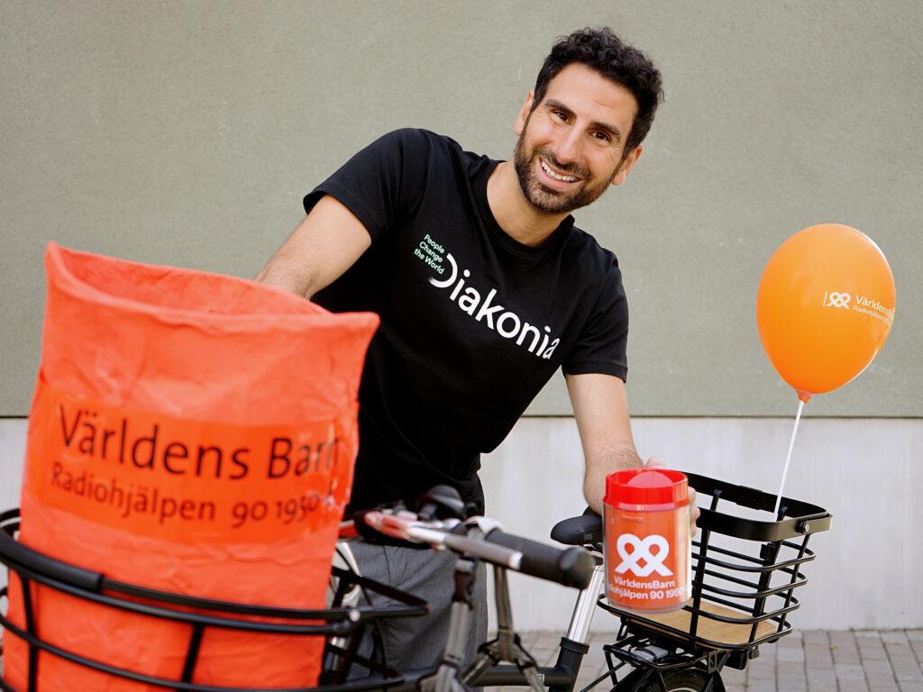 Stephan Wilson står med sin cykel i Diakonia-tröja och med en insamlingsbössa i handen.