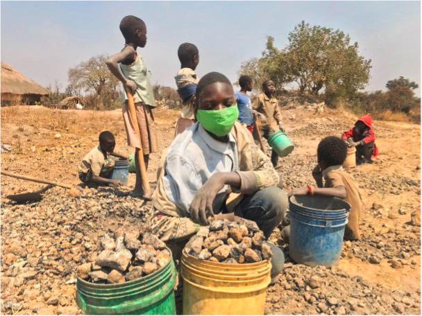 En pojke med munskydd sitter på marken, framför sig har han några hinkar med sten.