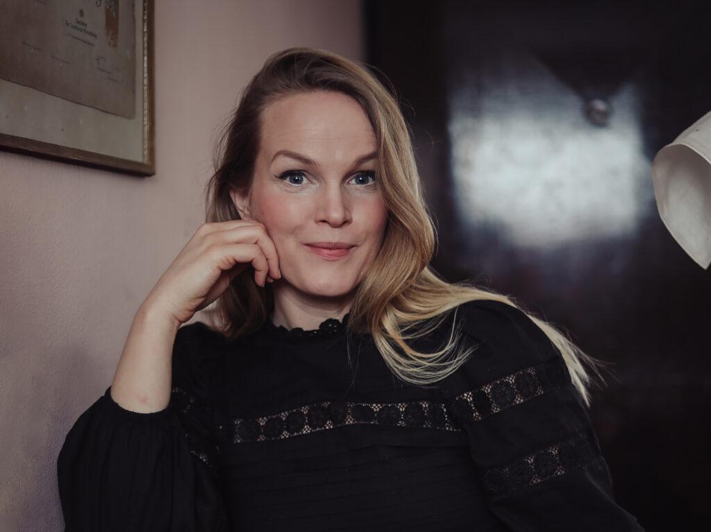 Ett porträtt av Emma Sundh som sitter i mörka kläder med handen mot hakan.