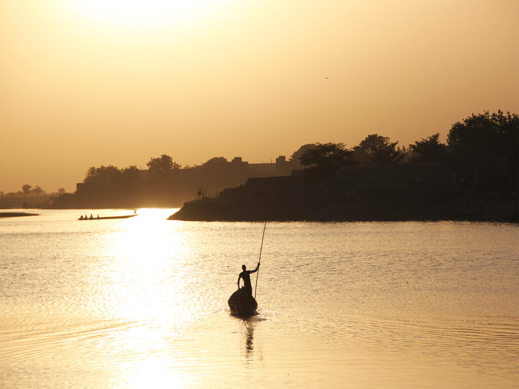 En båt i motljus i solnedgång.