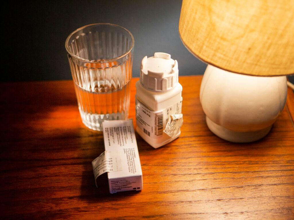 Ett nattduksbord med ett glas, medicinpaket och en lampa.