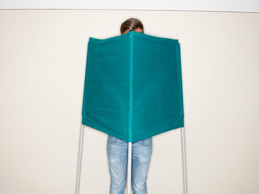 En person i ett röstbås.