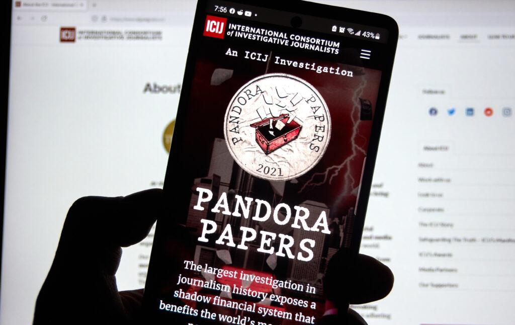 Mobiltelefon framför skärm med avslöjandet om pandora papers.