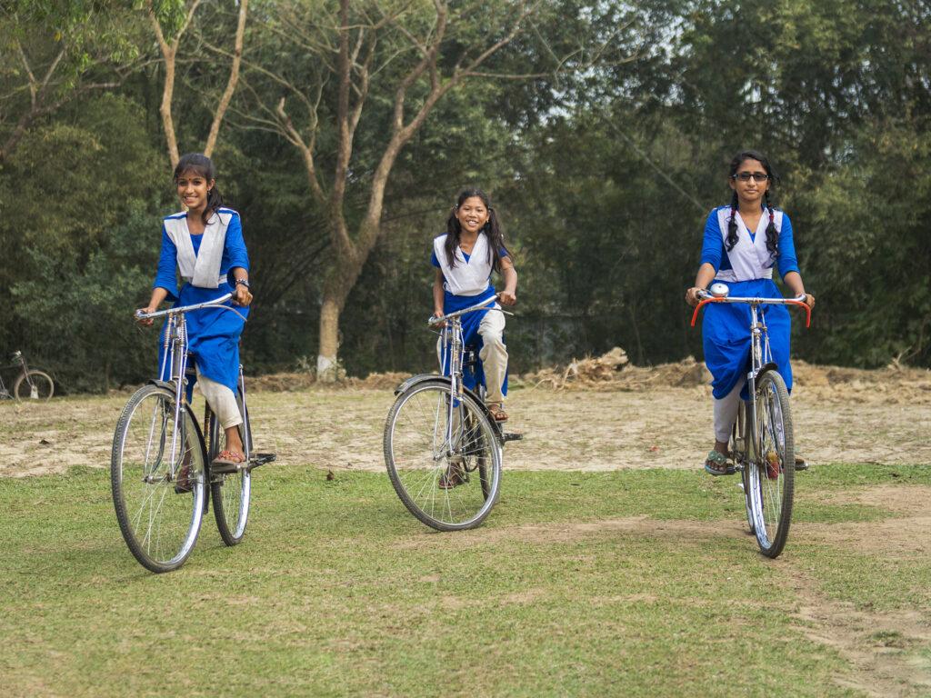 Tre flickor i skoluniformer från Bangladesh cyklar.