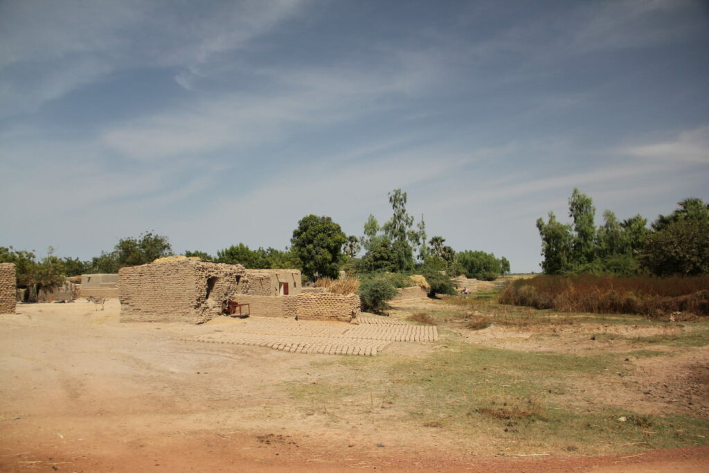 A hut of bricks and in the background trees.