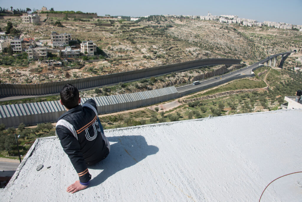 A person on a rooftop overlooking the high concrete wall and settlements on a hill.
