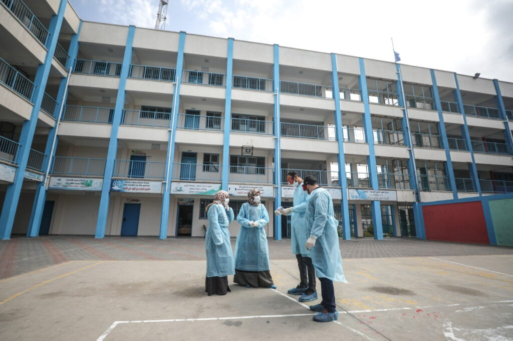 Health workers in protective gear discussing with each other, and in the background a tall building.