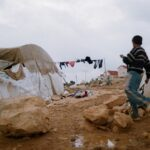 A boy walking through a camp with tents.