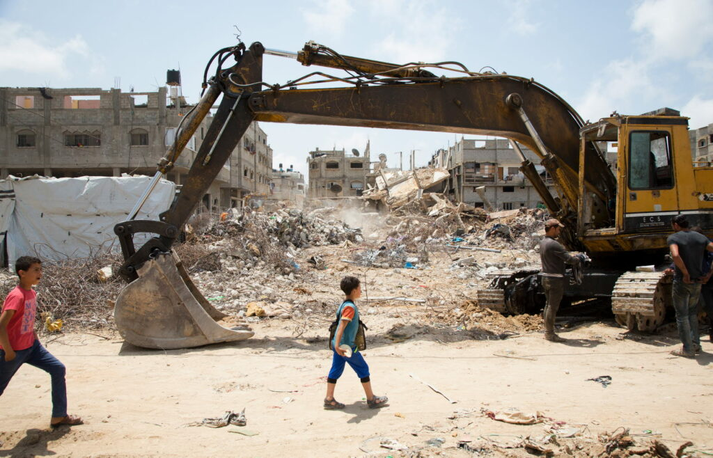 A child passes by a dredger with rubble in the background.