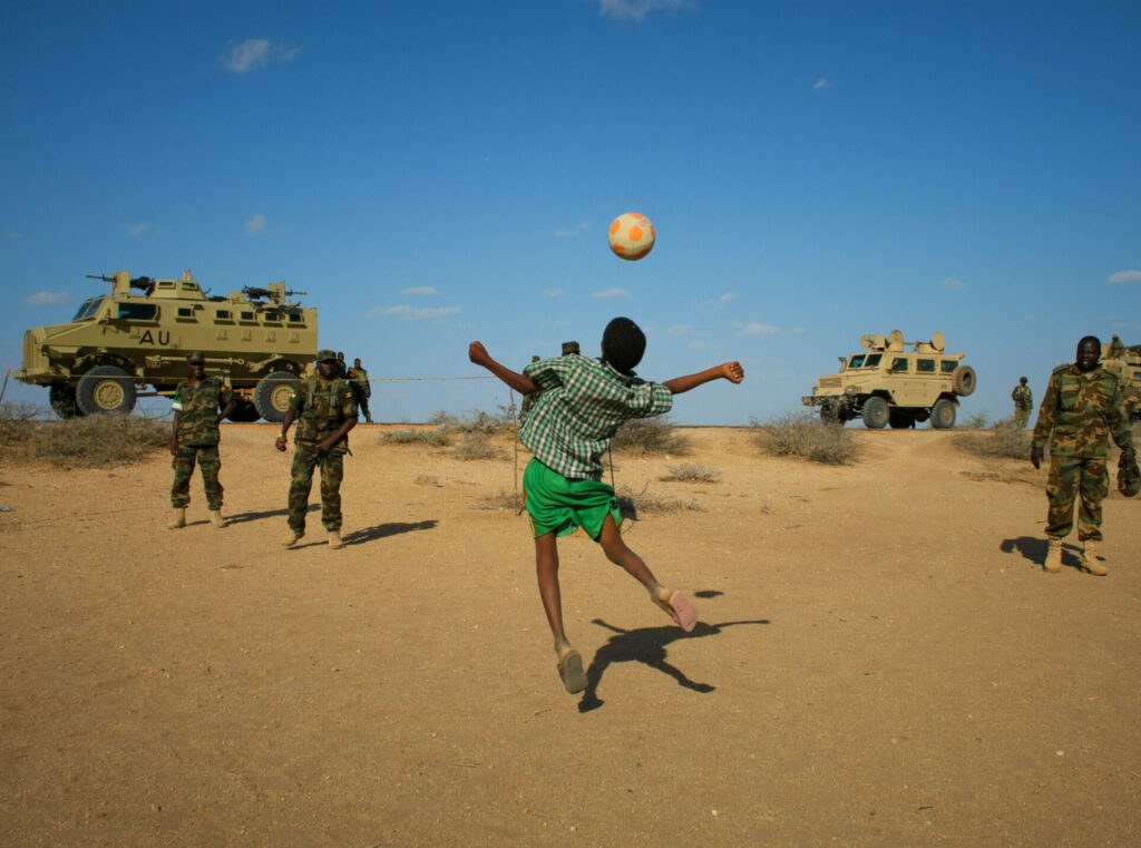 A boy playing with a ball, with soldiers and military vehicles in the background.