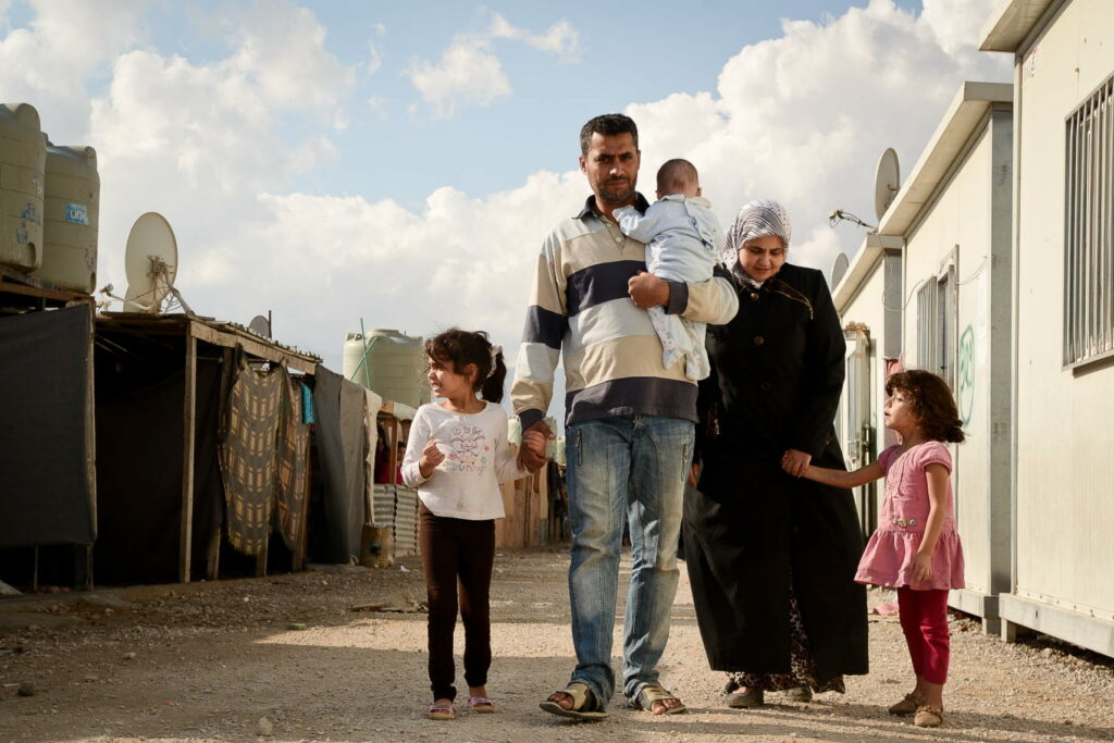 A family walking through the street in a camp of barracks.