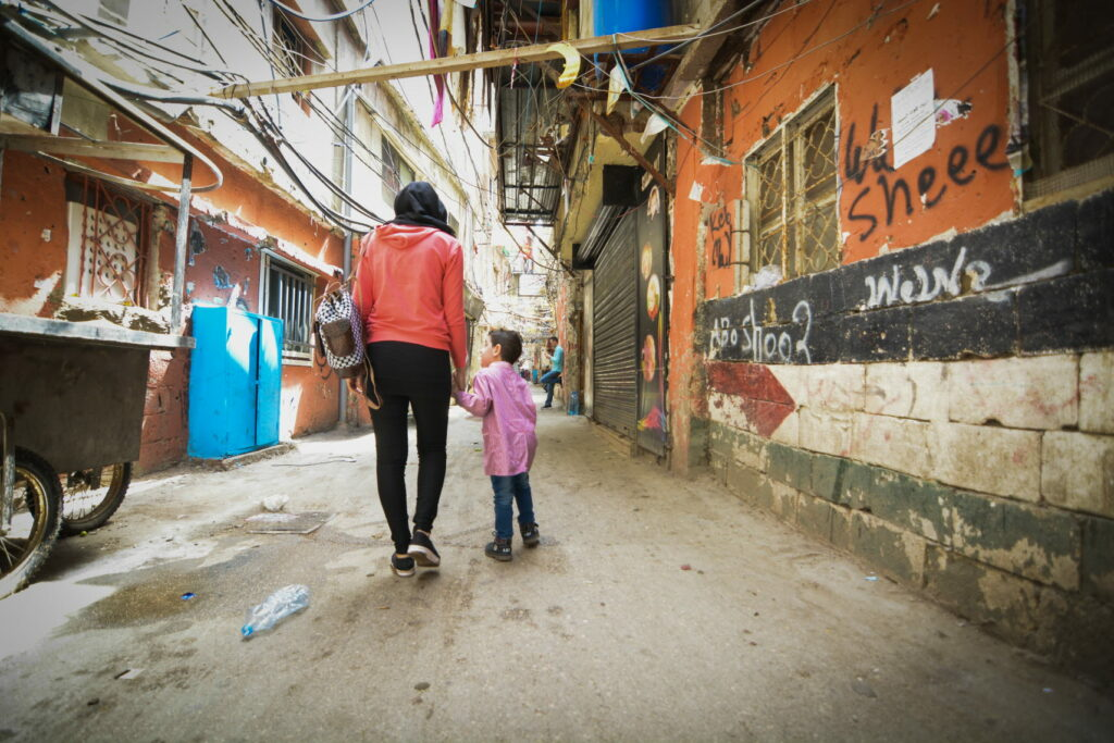 A woman and a child walking through a street.