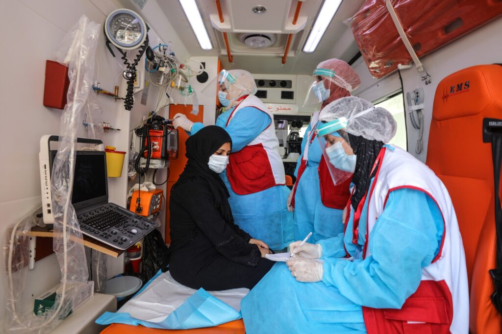 Medial personnel examine a woman in an ambulance car.